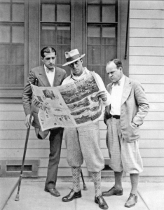American writer Laurence Stallings (left) and American film director Raoul Walsh (center) read the New York Times.  Photo circa 1926.